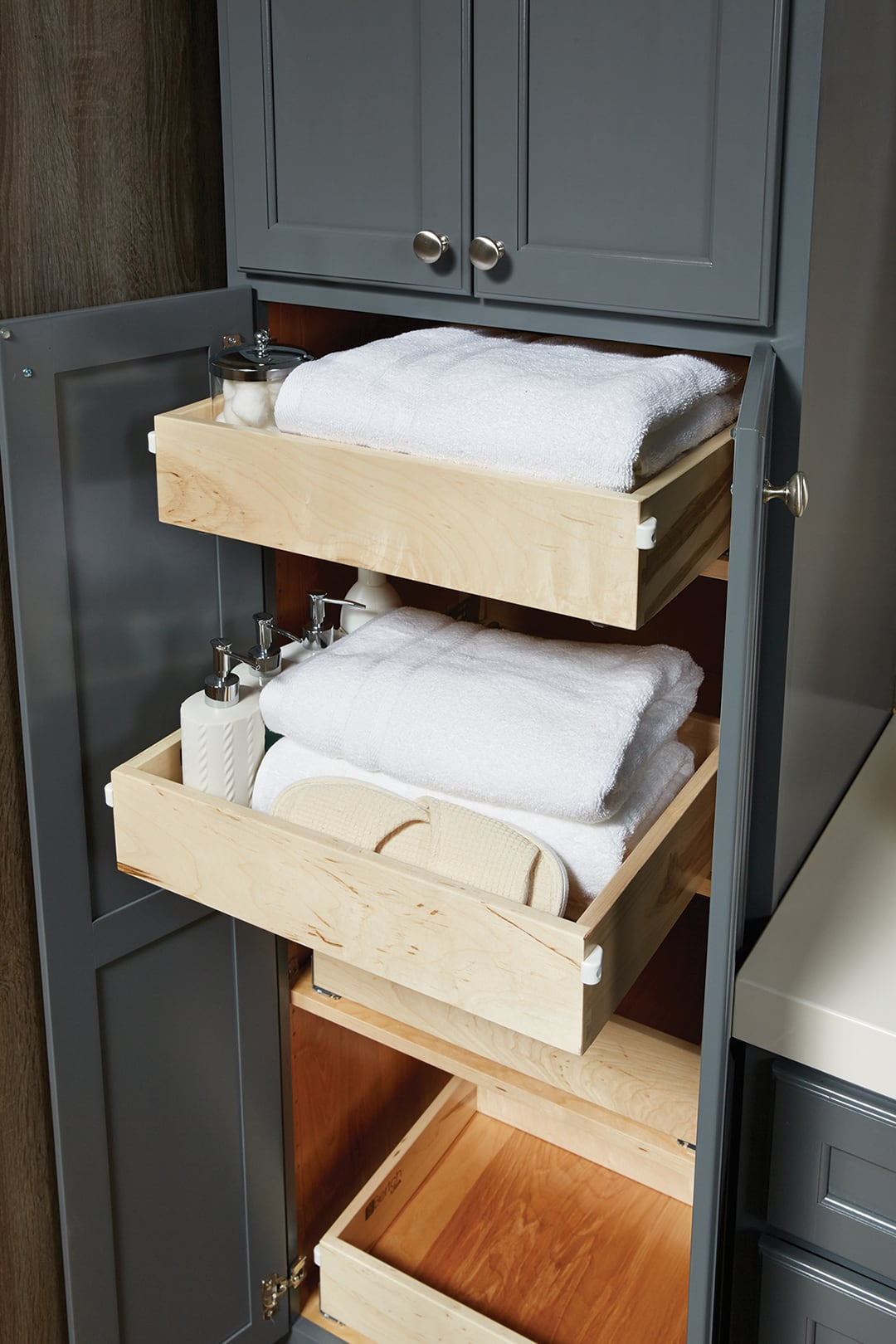 concealed drawers behind the doors of a bathroom linen cabinet